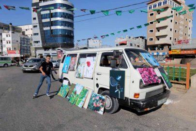 رسام يعرض لوحاته على متن سيارة في الشوارع والأسواق